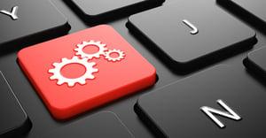 Cogwheel Gear Mechanism on Red Button on Black Computer Keyboard.