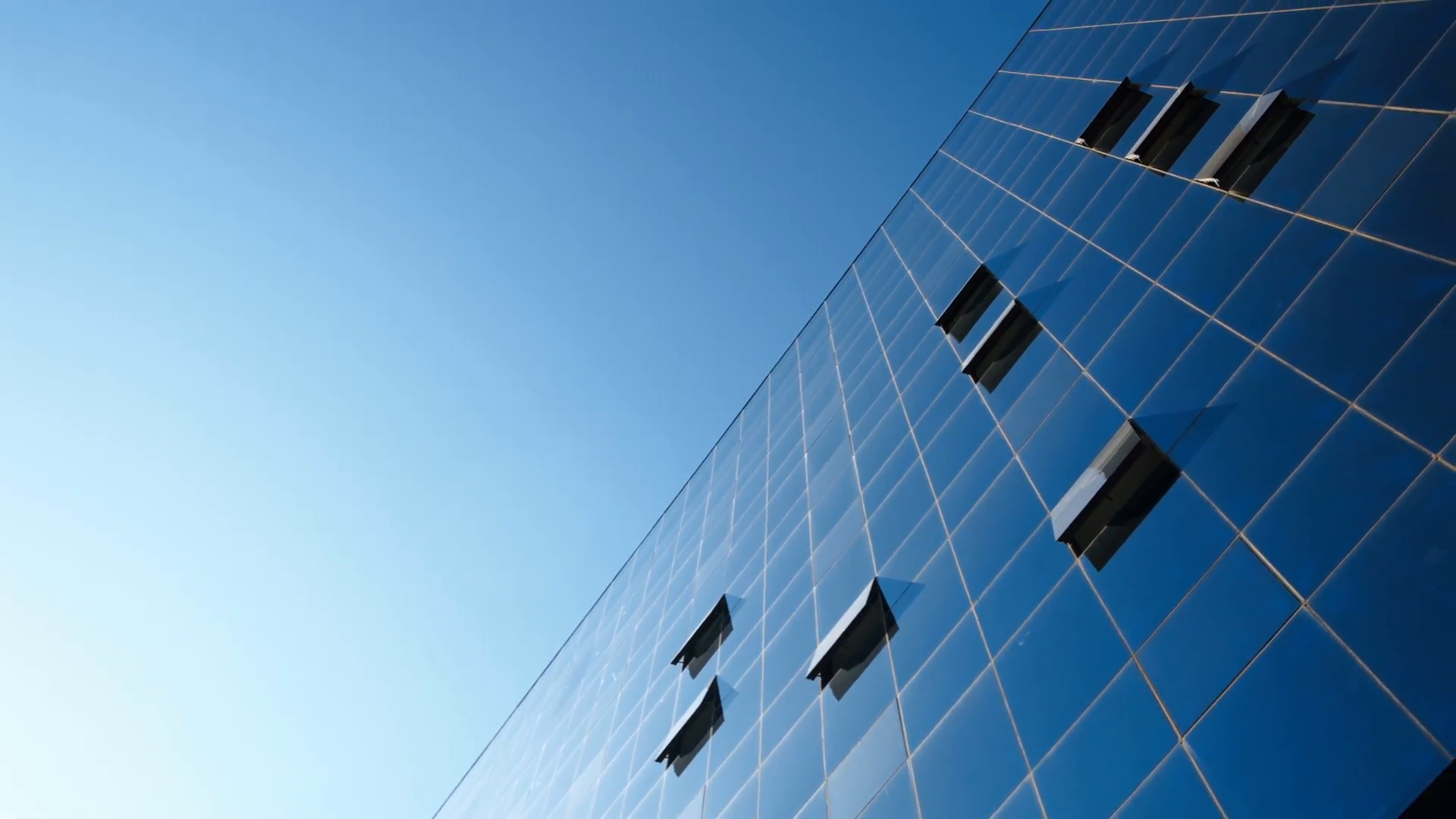 some-open-windows-in-an-office-building-with-the-blue-sky-as-background-and-a-glass-facade-camera-pan-movement-from-the-left-side_4jomzq3u__F0000